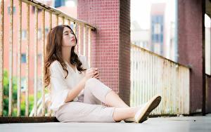 Фотографии Азиатка Забором Размытый фон Шатенки Сидящие Ног молодые женщины