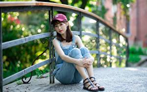Картинка Азиаты Забор Шатенка Кепка Сидя Рука Ноги Боке молодая женщина