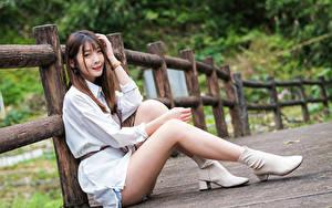 Картинка Азиатки Забором Сидит Ноги Улыбается Взгляд молодые женщины