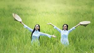 Фотография Азиаты Трава Брюнетка Двое Шляпа Руки Девушки
