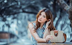 Фото Азиатки Сумка Боке Шатенка Смотрит Руки Красивая молодая женщина