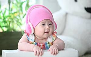 Фото Азиаты Младенцы Размытый фон Шапки Наушники Рука Смотрят Дети