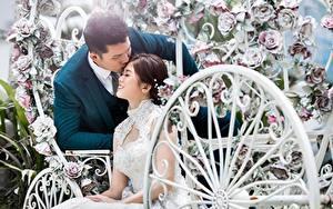 Картинка Азиатка Мужчина Влюбленные пары Свадьба Двое Сидящие Жених Невеста Целует молодые женщины