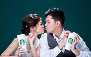 Картинка Азиатка Мужчина Влюбленные пары Цветной фон Двое Поцелуй Шатенки starbucks молодые женщины
