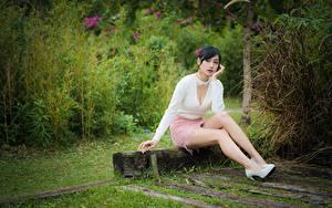 Фотографии Азиатки Поза Сидящие Ноги Юбки Декольте Брюнетка блузка молодые женщины