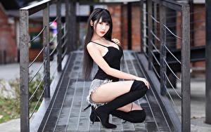 Фотографии Азиатки Позирует Сидящие Сапогов Шорт Майки Брюнетки Смотрит Миленькие Красивая девушка