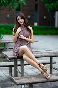 Фотографии Азиатки Сидит Платье Ноги Взгляд Размытый фон Красивые молодая женщина