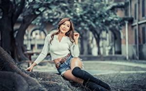 Фото Азиатка Сидя Шорт Ноги Сапогов Руки Шатенка Размытый фон Красивые Девушки