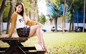 Фото Азиатки Сидит Столы Ног Юбки Улыбка Смотрят молодая женщина