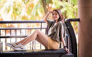 Обои Азиатки Улыбается Сидящие Ног Кроссовках Шорт Футболке Смотрит девушка
