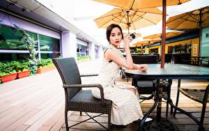 Картинка Азиатка Стол Сидящие Фотоаппарат Платье Взгляд девушка