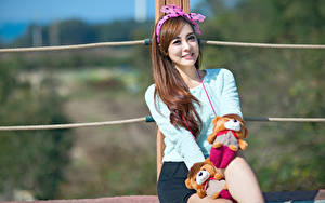 Фото Азиатка Игрушки Размытый фон Бантик Взгляд Сидит Улыбается молодые женщины