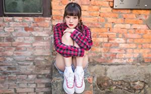 Картинка Азиатка Стены Кирпичный Сидящие Ног Рубашка Кроссовки Девушки