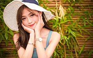 Обои Азиаты Наручные часы Шляпы Шатенки Руки Взгляд Улыбается молодые женщины