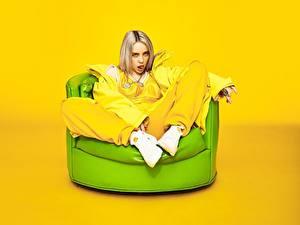 Фотографии Цветной фон Кресло Сидящие Блондинка Взгляд Billie Eilish Знаменитости Девушки