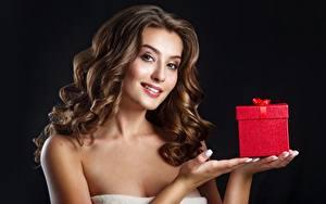 Фотография На черном фоне Рука Коробки Подарок Шатенки Смотрит Прически Волос девушка