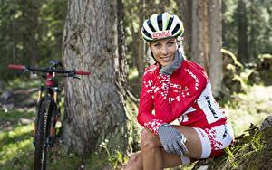 Картинки Блондинки Велосипед В шлеме Улыбка Сидящие Униформа Рука Перчатки молодые женщины Спорт