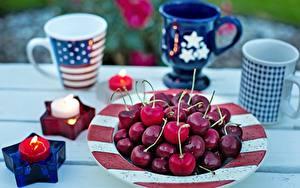 Фото Вишня Свечи Огонь Кружки Тарелке Звездочки Размытый фон Американский Еда