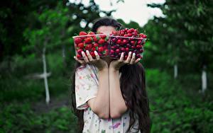 Фотографии Вишня Клубника Размытый фон Рука Коробка Две Еда