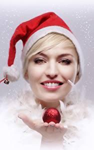 Фотографии Новый год Блондинка Шапки Улыбка Смотрит Руки Шарики Девушки