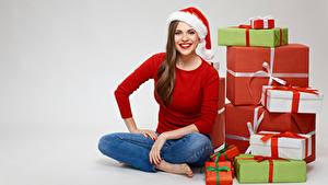 Картинки Рождество Шатенки Шапка Сидящие Смотрит Улыбается Подарок Сером фоне девушка