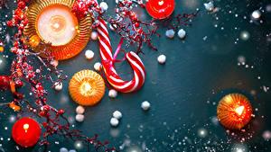 Картинка Новый год Свечи Ягоды Леденцы Цветной фон Ветки Еда