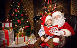 Фотографии Рождество Новогодняя ёлка Подарок Санта-Клаус Мальчик Шапка Сидящие