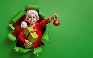 Картинка Рождество Цветной фон Девочка Улыбается Шапка Шар Подарок Рука ребёнок
