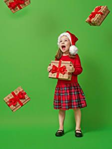 Фотографии Рождество Цветной фон Девочка Шапка Подарок Кричит ребёнок