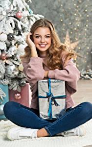 Обои для рабочего стола Новый год Милая Улыбается Смотрят Подарки Сидит Шатенки девушка