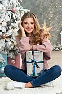 Картинка Новый год Милая Улыбается Смотрят Подарки Сидит Шатенки девушка