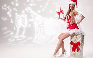 Фото Рождество Подарки Бантик Русые Униформа Сидящие Шапки Ноги Туфли Девушки