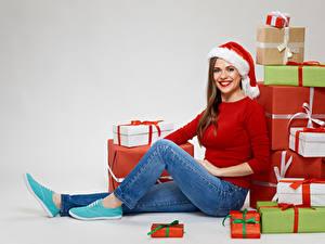 Обои Рождество Серый фон Шатенка Подарки Смотрит Улыбка Шапки Джинсы Сидящие Девушки
