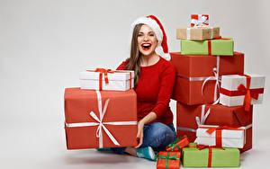 Фотография Рождество Сером фоне Шатенки Счастье Шапка Подарок Смотрит