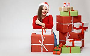 Картинки Новый год Серый фон Шатенка Улыбка Шапки Подарки Девушки
