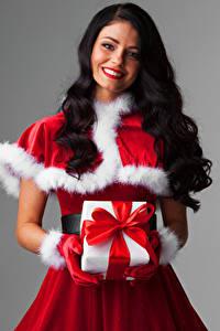 Фото Рождество Серый фон Брюнетка Улыбка Подарки Униформа Волосы Бантик Девушки