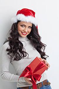 Картинка Рождество Серый фон Брюнетка Улыбка Шапки Подарки Девушки