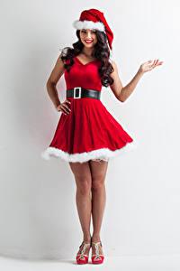 Картинка Новый год Серый фон Брюнетка Униформа Платье Шапки Улыбка Руки Девушки