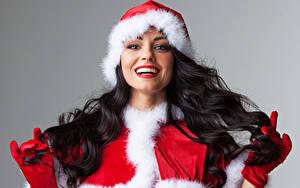 Картинка Новый год Серый фон Брюнеток В шапке Улыбается Смотрит Перчатки Красными губами