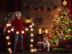 Обои Рождество Праздники Девочка Грудной ребёнок Две Елка Улыбка Электрическая гирлянда Подарки Шар Фонари