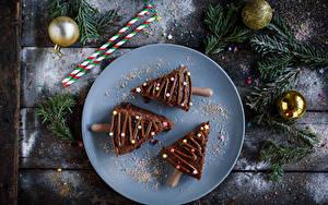 Картинки Новый год Пирожное Шоколад Доски Тарелке Трое 3 Новогодняя ёлка Ветка Шарики