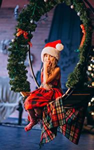 Картинки Рождество Девочка Сидя Ветки Шапки ребёнок