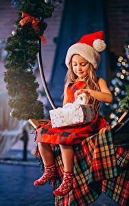 Фотографии Новый год Девочки Сидящие Шапка Подарки На ветке Дети