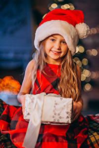 Обои Рождество Девочка Улыбка Подарок Шапки Взгляд ребёнок