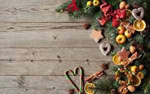 Обои Новый год Леденцы Яблоки Печенье Корица Бадьян звезда аниса Доски Ветки Бантик Шаблон поздравительной открытки Еда