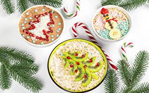 Картинка Новый год Леденцы Оригинальные Овсяная Мюсли Киви Гранат Белый фон Ветвь Елка Снеговик Пища