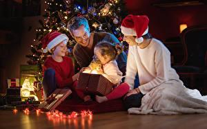 Фотография Рождество Мужчины Мать Девочки Мальчики Улыбка Подарки Шапки Электрическая гирлянда Ребёнок