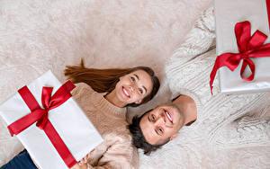 Фотографии Новый год Мужчины Двое Взгляд Улыбка Шатенка Подарки Девушки
