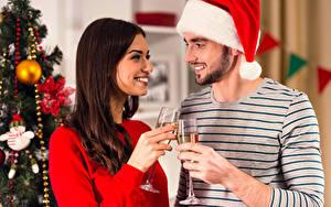 Картинка Новый год Мужчины Вино Двое Шатенка Улыбка Бокалы Шапки Девушки