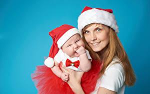 Картинки Рождество Мать Цветной фон Улыбка Шапки Младенец Смотрит Девушки
